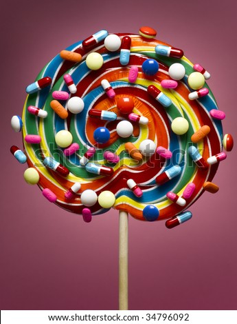Lollipop coated with pills, close-up - stock photo