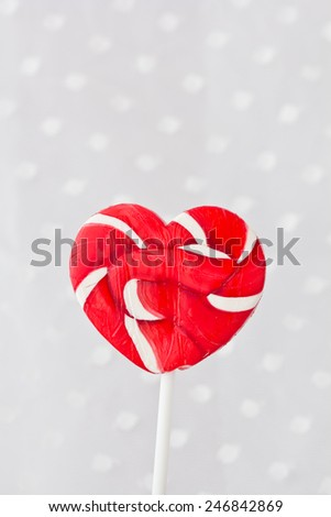 Lollipop in Heart Shape. Valentines Day Candy on white dot fabric background - stock photo