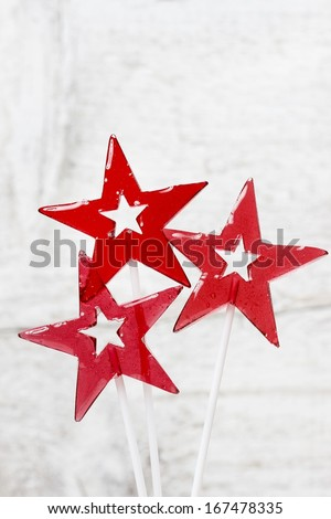 Lollipops in star shape on wooden background. Copy space - stock photo