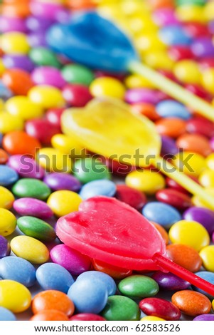 lollipops lying on colored candies - stock photo