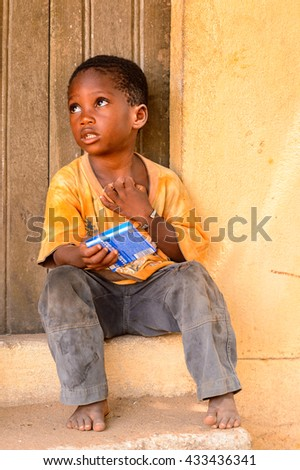LOME, TOGO - MAR 9, 2013: Unidentified Togolese little boy sits at the porch of a house. People of Togo suffer of poverty due to the unstable economic situation.