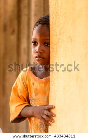 LOME, TOGO - MAR 9, 2013: Unidentified Togolese little girl stays near a house. People of Togo suffer of poverty due to the unstable economic situation.