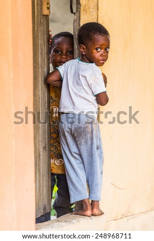 LOME, TOGO - MAR 9, 2013: Unidentified Togolese two little girls near a door of a local house. People of Togo suffer of poverty due to the unstable economic situation. - stock photo