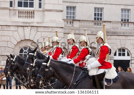 LONDON - APR 20: The colorful changing of the guard ceremony at Buckingham Palace on April 20th, 2013 in London, UK. It is one of England's most popular visitor attractions. - stock photo