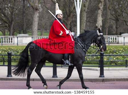 LONDON - APR 13: The colorful changing of the guard ceremony at Buckingham Palace on April 13th, 2013 in London, UK. It is one of England's most popular visitor attractions. - stock photo