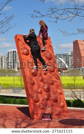 LONDON - APRIL 18, 2015. Children enjoying the climbing wall in the park at Stratford, an area currently experiencing a huge regeneration programme in the Borough of Newham, east London, UK. - stock photo