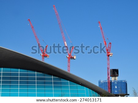 LONDON - APRIL 18, 2015. Cranes tower above the Aquatics Centre transforming the landscape of Stratford; part of a huge regeneration programme from industrial wasteland in east London, UK. - stock photo