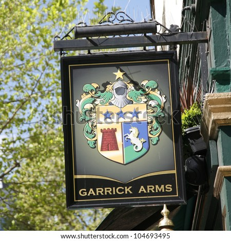 LONDON - APRIL 30: English pub sign, Public house, known as pub, is focal point of community, on April 30, 2012, London, UK. Pub business, now about 53,500 pubs in UK, has been declining every year - stock photo