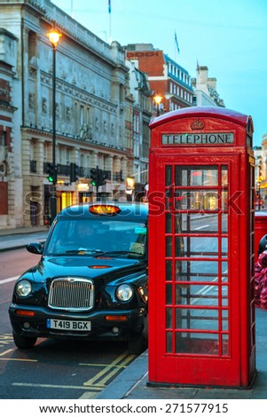 LONDON - APRIL 12: Famous red telephone booth and taxi cab on April 12, 2015 in London, UK. The red telephone box, a telephone kiosk for a public telephone designed by Sir Giles Gilbert Scott. - stock photo