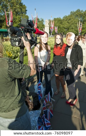 LONDON - APRIL 27: Fans outside Buckingham palace with royal family masks to celebrate the royal wedding celebration to take place April 29. April 27, 2011 in London, England. - stock photo