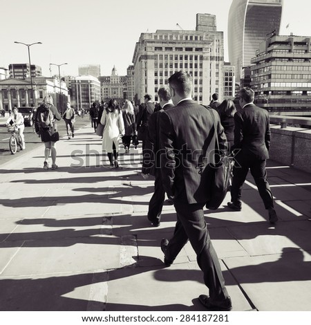 LONDON - APRIL 27 : London commuters on April 27, 2015 in London, UK. People walking across the London Bridge early in the morning.  - stock photo