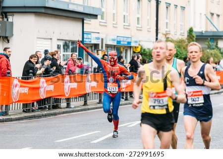 LONDON - APRIL 26: Man in Spiderman costume runs the Virgin Money London Marathon on April 26, 2015 in Isle of Dogs, London, England, UK. - stock photo