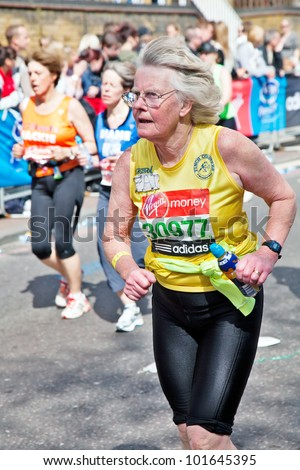 LONDON - APRIL 22: One of the older female participants in the 2012 London marathon starts the climb uphill towards the 23 mile marker at Tower underground station on April 22, 2012 in London - stock photo