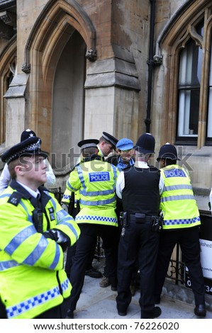 LONDON - APRIL 29 - Police arrest a man for breaking through the security cordon at the Royal Wedding of Prince William and Kate Middleton at Westminster Abbey in London, April 29, 2011 - stock photo