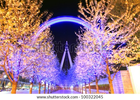 LONDON - APRIL 15: Trees lead to the London Eye, on April 15, 2012 in London. The largest Ferris wheel in Europe, structure of the London Eye is 135 M. tall and the wheel has a diameter of 120 M. - stock photo