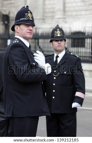 LONDON - APRIL 17: Two police officers oversee the public at the funeral service for Margaret Thatcher at St. Paul's Cathedral on April 17, 2013 in London. - stock photo