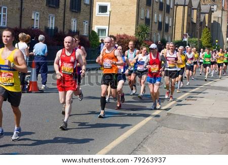 LONDON - APRIL 17: Unidentified men run the London marathon on April 17, 2011 in London, England, UK. The marathon is an annual event. - stock photo
