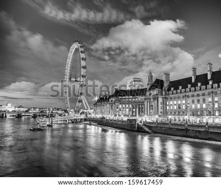 London at night. Thames river with The Eye Panoramic Wheel. - stock photo