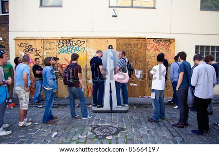 LONDON - AUG 28: men queue up at a open-sky toilet during the  Notting Hill Carnival on August 29, 2011 in London, England. - stock photo