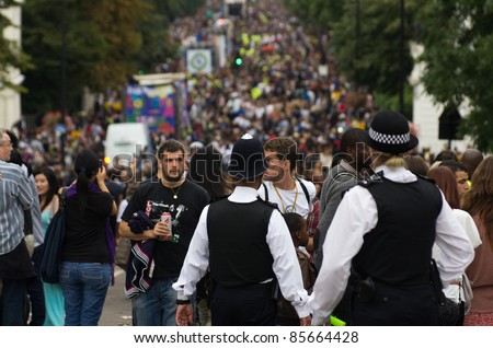 LONDON - AUG 28: policemen patrol the street of  Notting Hill during the famous annual caribbean  Carnival on August 29, 2011 in London, England. - stock photo