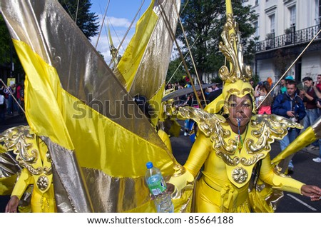 LONDON - AUG 28: yellow dressed performer parades in the Notting Hill Carnival on August 29, 2011 in London, England. - stock photo
