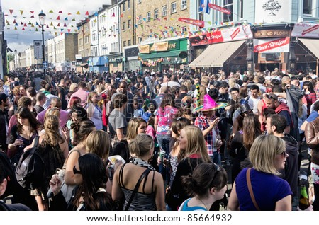 LONDON - AUG 28: youngsters crowd on the street of Notting Hill during the annual Carnival on August 29, 2011 in London, England. - stock photo