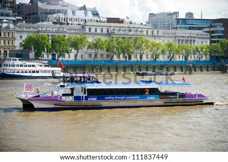 LONDON-AUGUST 6: A City Cruises tour boat sails on the Thames River on August 6, 2012 in London, England. Thames is the longest river in England with 346 km (215 miles)  long. - stock photo
