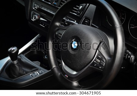 LONDON - AUGUST 10: BMW passenger car interior showing steering wheel and gear shift. August 10, 2015 in London, UK. - stock photo