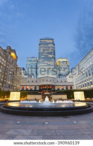 LONDON - AUGUST 21: Cabot Square in the modern Canary Wharf quarter with its banks and skyscrapers at night on August 21, 2013 - stock photo