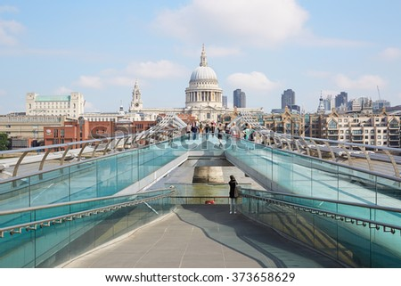LONDON - AUGUST 8: Millennium bridge with people walking and St Paul cathedral in a summer morning on August 8, 2015 in London. The footbridge crosses the river Thames linking Bankside with the City.  - stock photo