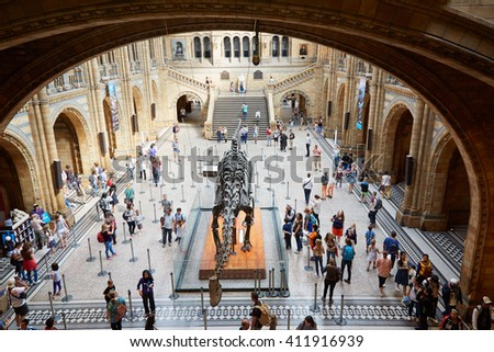 LONDON - AUGUST 7: Natural History Museum interior with people and tourists and dinosaur skeleton on August 7, 2015 in London, UK. The museum hosts a vast range of specimens. - stock photo