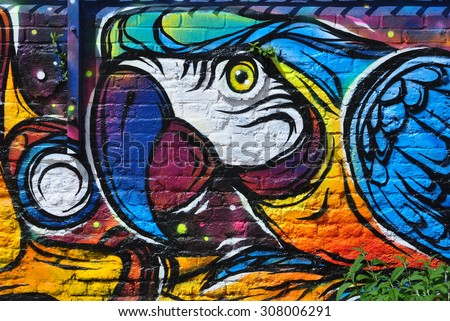 LONDON - AUGUST 1, 2015. Street art on an old brick wall in the Nomadic Community Gardens at Shoreditch in the Borough of Tower Hamlets, an area renown for its public painting in east London, UK. - stock photo