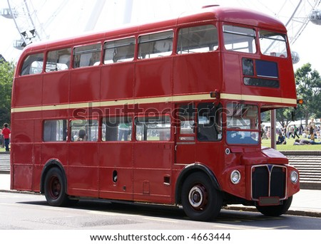London Bus with faint outline of the London Eye in the Background - stock photo