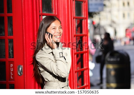 London business woman on smart phone by red phone booth. Communication concept with young multiracial Asian businesswoman on smartphone or mobile phone in London, England, United Kingdom. - stock photo