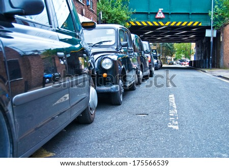 London cabs lined up on the street waiting for fares. - stock photo