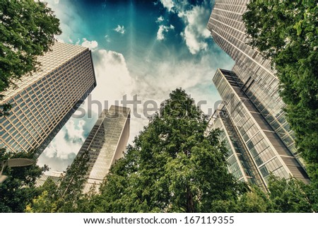 London, Canary Wharf. Beautiful view of Skyscrapers and trees from street level. - stock photo