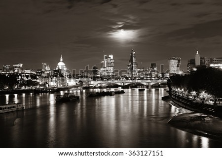 London cityscape with urban buildings and moon over Thames River at night - stock photo