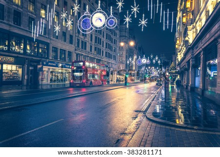 LONDON - DEC 6, 2015 : Cinematic look of Christmas Lights Display on Oxford Street and red bus on December 6, 2015, London, UK. - stock photo
