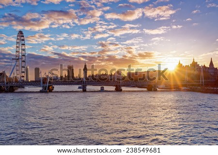 LONDON - DEC 14: Panoramic view from Waterloo bridge on London eye and Houses of Parliament at sunset on December 14th, 2014 in London, England. It is one of the most popular attraction in London.  - stock photo