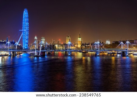 LONDON - DEC 14: Panoramic view from Waterloo bridge on London eye and Houses of Parliament at night on December 14th, 2014 in London, England. It is one of the most popular attraction in London.  - stock photo