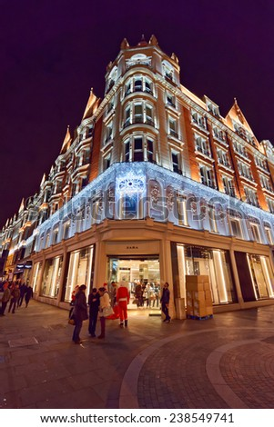 LONDON - DEC 14 : the building and street of Harrods pictured at Christmas time on December 14th, 2014, in London, UK. It was opened at 1824 and now is one of the most famous luxury store in London.  - stock photo