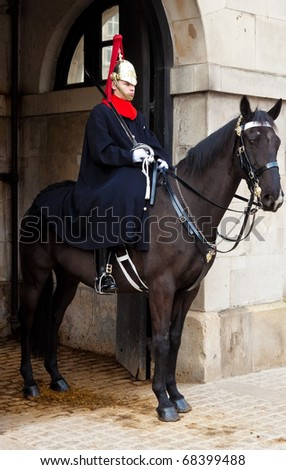 LONDON-DECEMBER 15: A cavalry trooper posted outside the Horse Guards December 15,2010 in London.Keeping with the tradition,two mounted guards are posted from 10am to 4 pm and are relieved every hour - stock photo