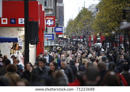 LONDON - DECEMBER 11: The famous Oxford Street pack with crowds of tourists and locals doing their last minute Christmas shopping December 11, 2010 in London, United Kingdom. - stock photo