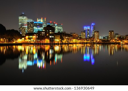 London docklands business district illuminated at night with reflections