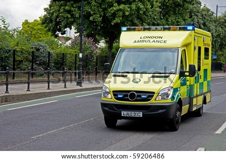 LONDON, ENGLAND - AUGUST 14: Emergency Ambulance speeds along street in London in response to an emergency call on August 14, 2010 in London. - stock photo