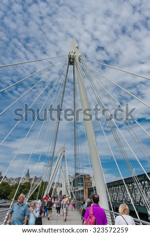 LONDON, ENGLAND, AUGUST 02, 2015;London landmarks, viewed from the Jubilee Bridge Dual pedestrian bridges constructed on either side of the Hungerford rail bridge across the river. - stock photo