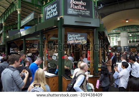 London, England - August 20, 2015: Staff can be seen working as people surround a seafood stall in Borough Market, London. The market has traded in Southwark, London for more than 250 years - stock photo