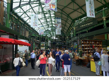London, England - August 20, 2015: Visitors and shoppers in the covered section of Borough Market in London, England. The market has traded in Southwark, London for more than 250 years - stock photo