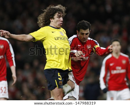 LONDON, ENGLAND. 31/03/2010. Barcelona player Carles Puyol fouls Arsenal player Cesc Fa?bregas during the  UEFA Champions League quarter-final between Arsenal and Barcelona at the Emirates Stadium - stock photo