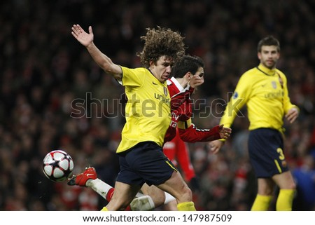 LONDON, ENGLAND. 31/03/2010. Barcelona player Carles Puyol fouls Arsenal player Cesc Fabregas (captain) and concedes a penalty during the UEFA Champions League quarter-final at the Emirates Stadium - stock photo